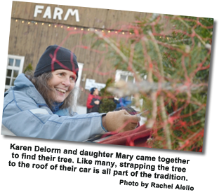 Fallowfield Tree Farm – Christmas Trees – cut-you-own or pre-cut – Photo of Karen Delome who came to Fallowfield Tree Farm with her daughter Mary to find their tree. Like many, strapping the tree to the roof of their car is all part of the tradition.