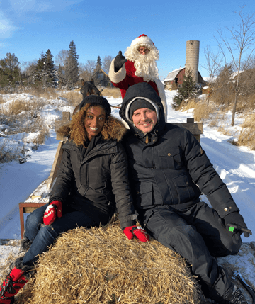 Photo of young couple and Santa taking a sleigh ride at Fallowfield Tree Farm