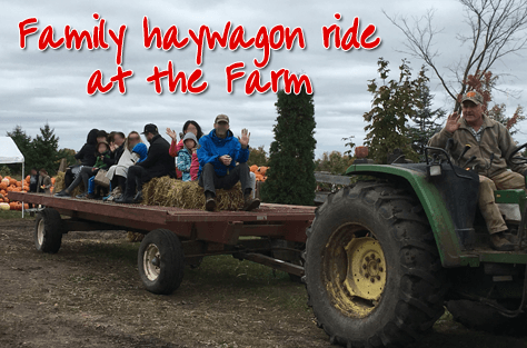 Photo of a happy family heading out for an early Fall hay ride at Fallowfield Tree Farm