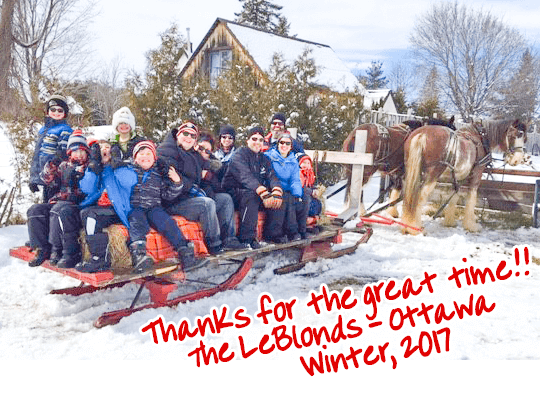 "The LeBlond family with friends, enjoying a horse-drawn sleigh ride at Fallowfield Tree Farm - with a caption in red handwriting font that reads ""Thanks for a great time!!, the Leblonds - Ottawa, Winter 2017"""